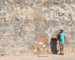 Äldre man (i gott skick!) framför gammal mur i Faro